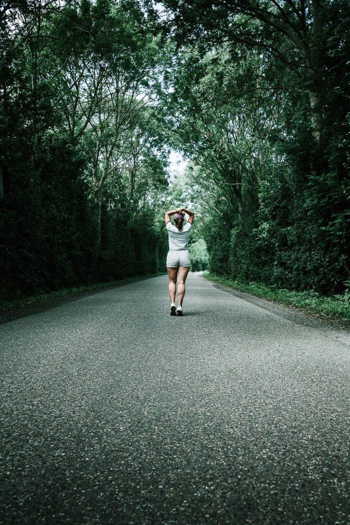 mangiare meno ragazza che cammina lungo una strada nel bosco